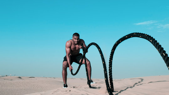 Man using battle ropes in the dessert